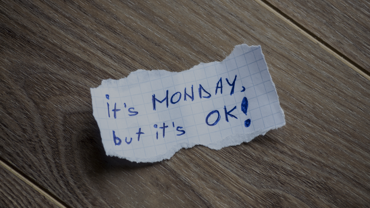 A piece of paper on a desk with it's Monday but it's ok! written on it.