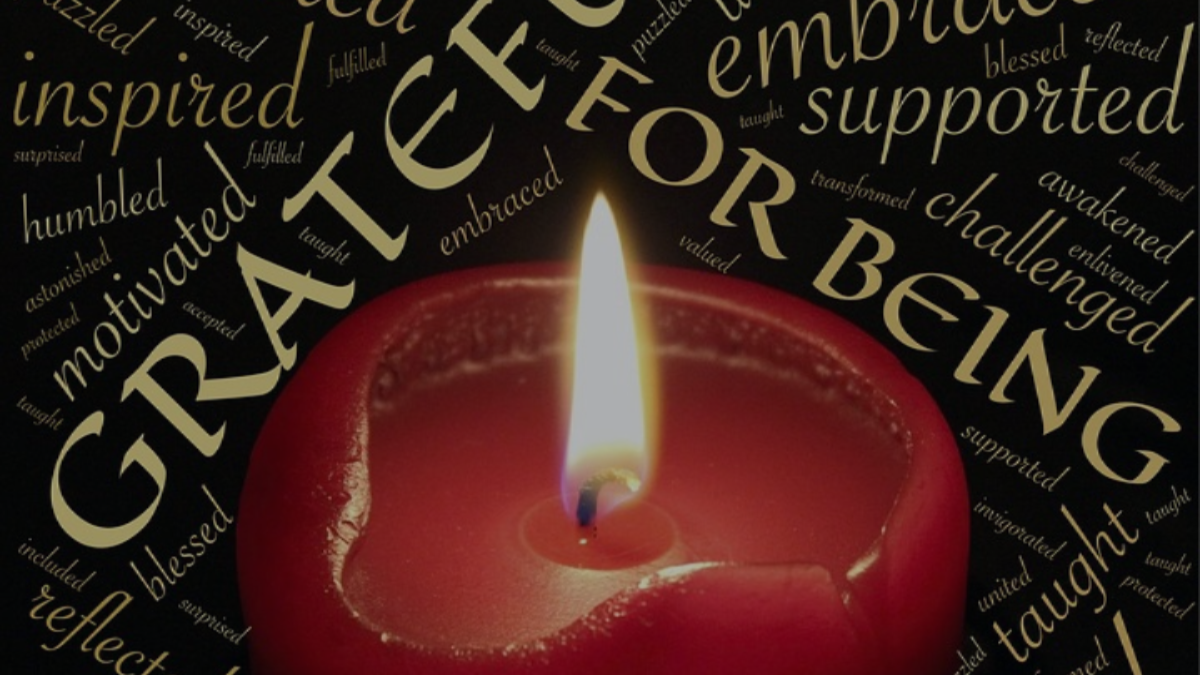 A burning candle with words of inspiration around it.