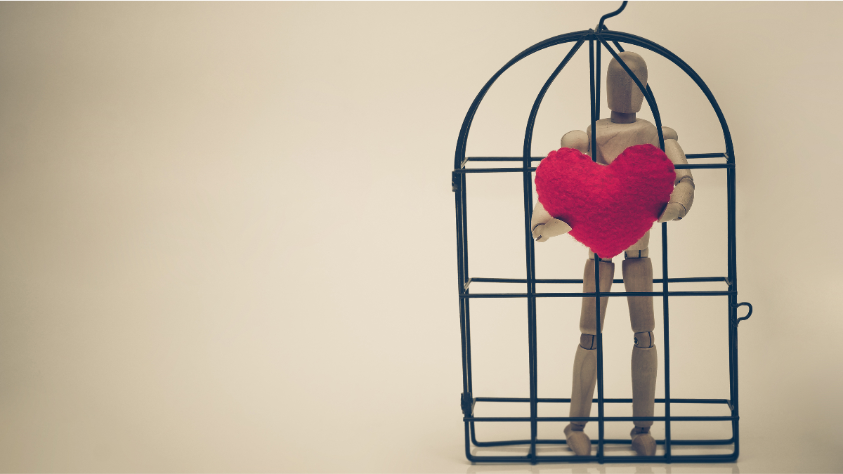 A figurine of a man trapped inside of a cage holding a heart which is outside the cage.